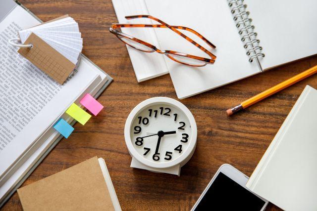 Bild mit Büchern, Brille, Uhr und Notizzetteln